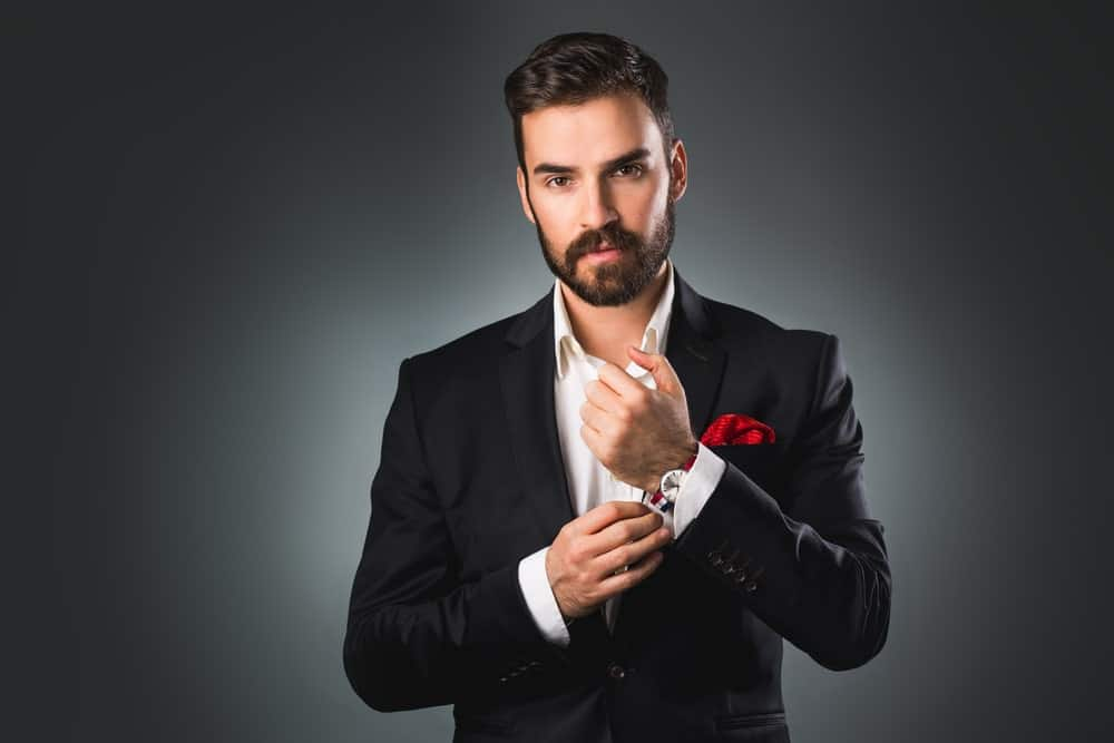 Handsome man wearing a suit and touching his sleeve.