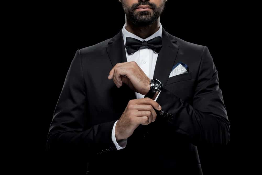 Cropped image of a man in a black tuxedo, tie, and wristwatch against a black background.