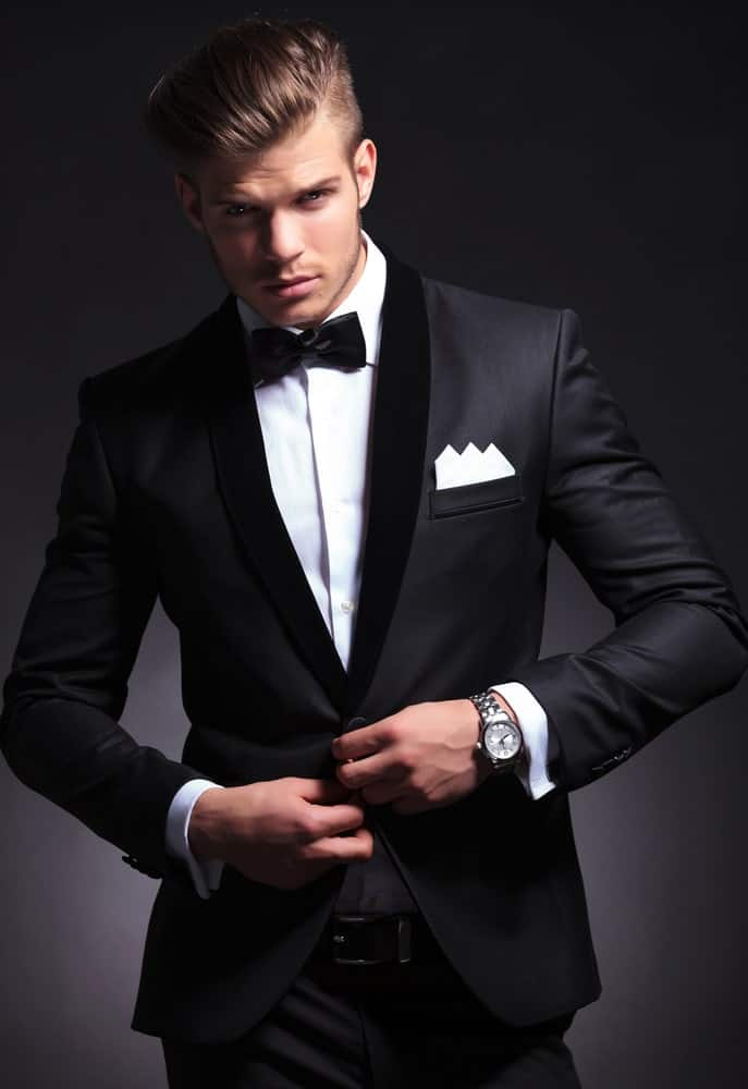 Young man in black bowtie tuxedo with a wristwatch unbuttoning his jacket.
