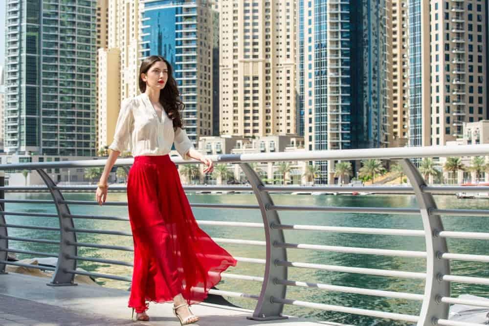 Woman in red maxi skirt walking alongside Dubai Marina Middle East.