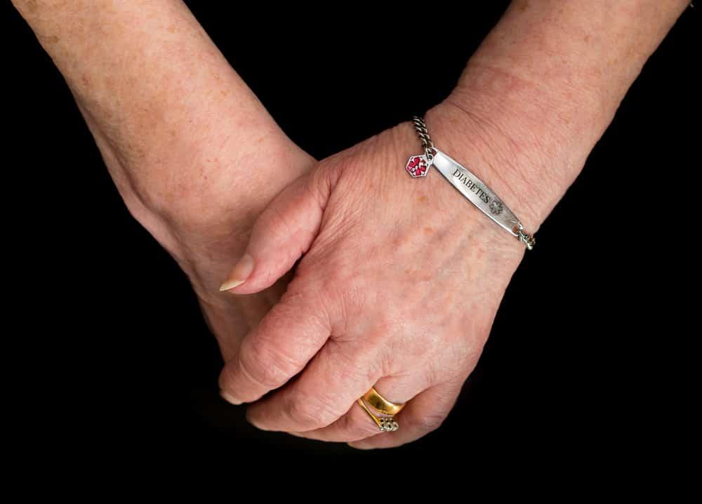 Elderly woman's hands wearing a medical alert bracelet for diabetes.