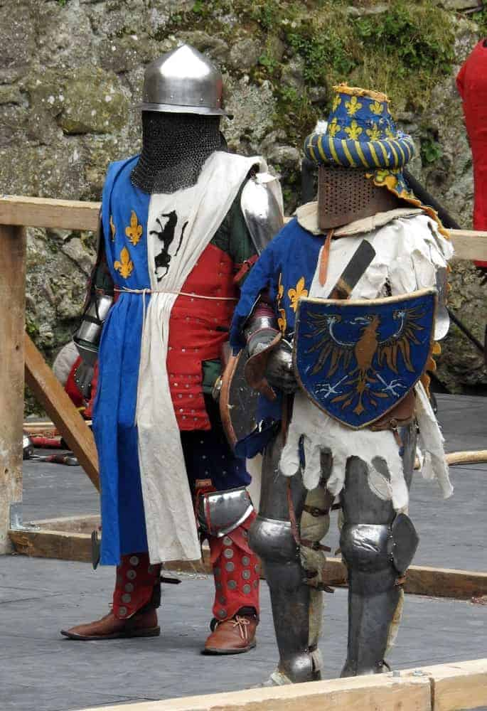 Two knights in full plate armor and decorative medieval surcoats.