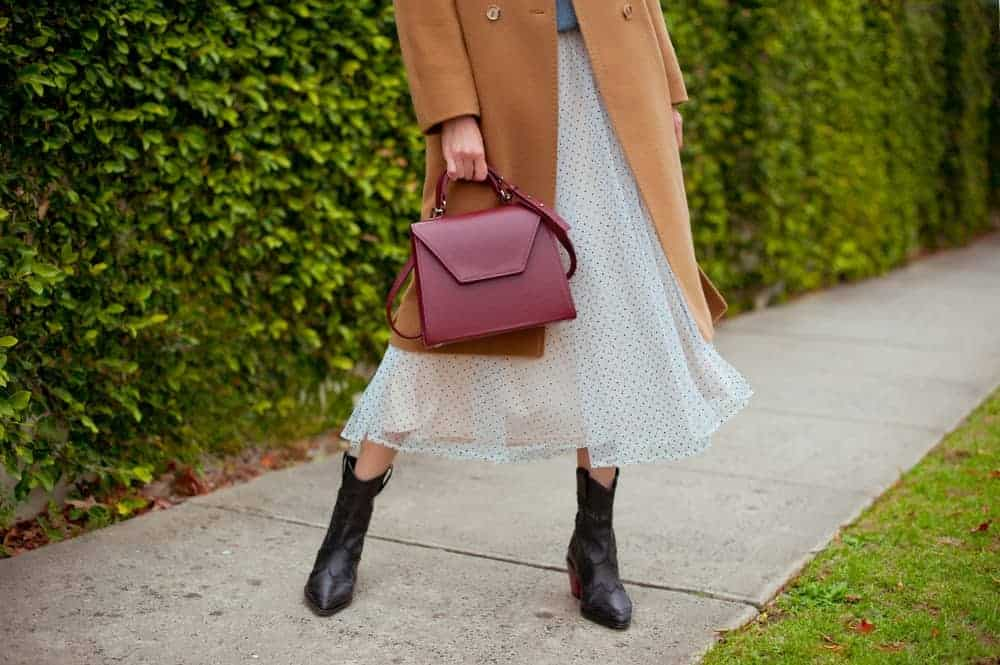 Woman in boots and tulle midi skirt holding a burgundy bag.