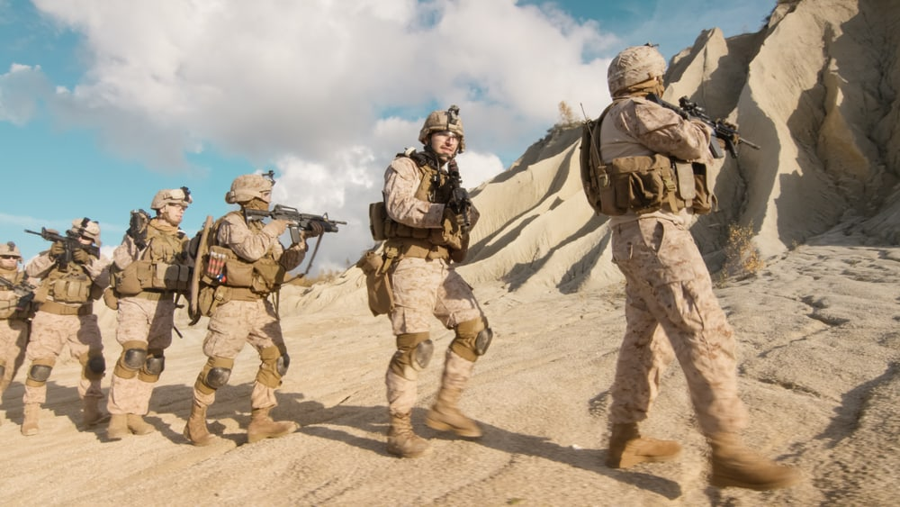 A squad of fully equipped and armed soldiers walking in single file in the desert.