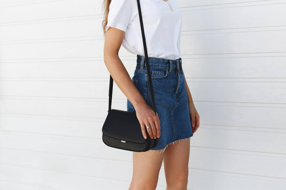 Woman wearing a white blouse, blue denim mini skirt, and small cross body bag.