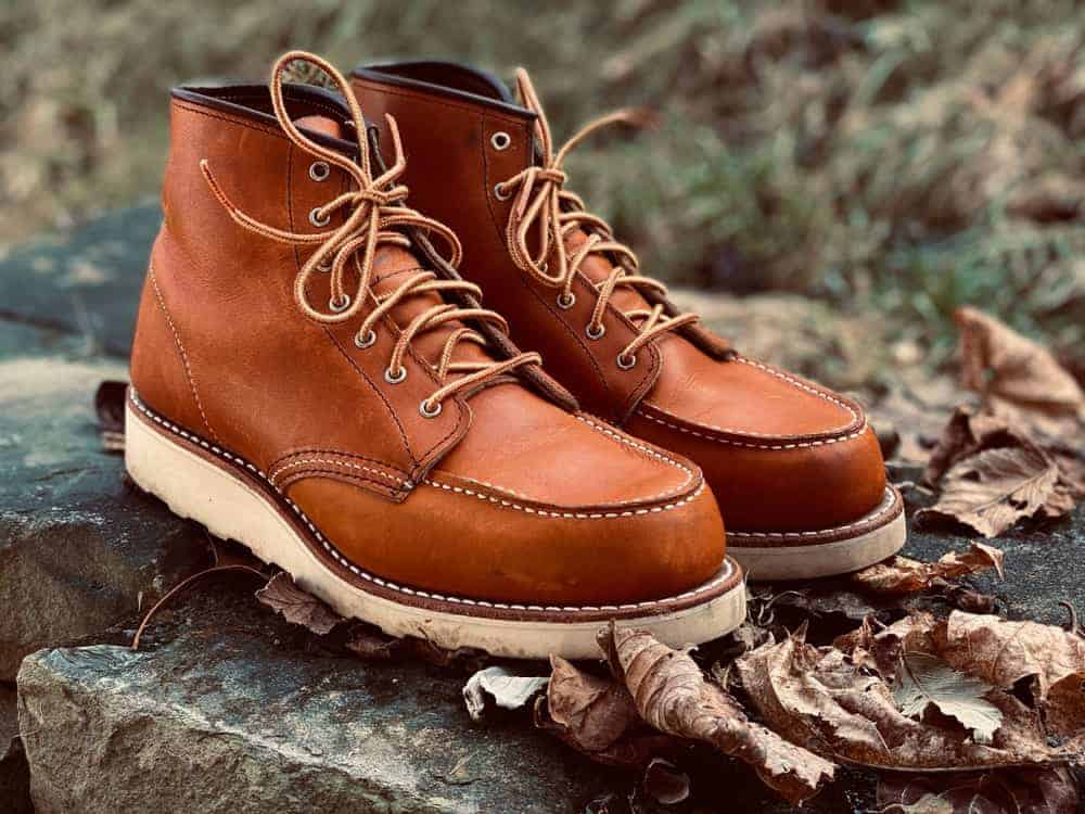 Moc toe brown leather shoes resting on large rocks.