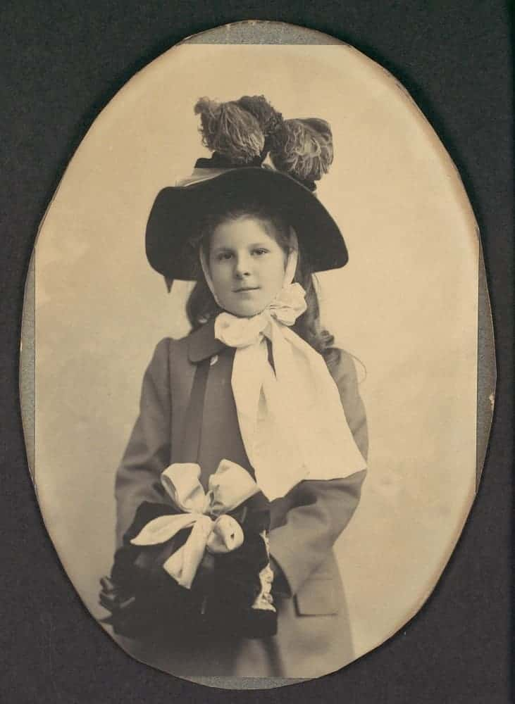 Girl in coat with hat and muff.