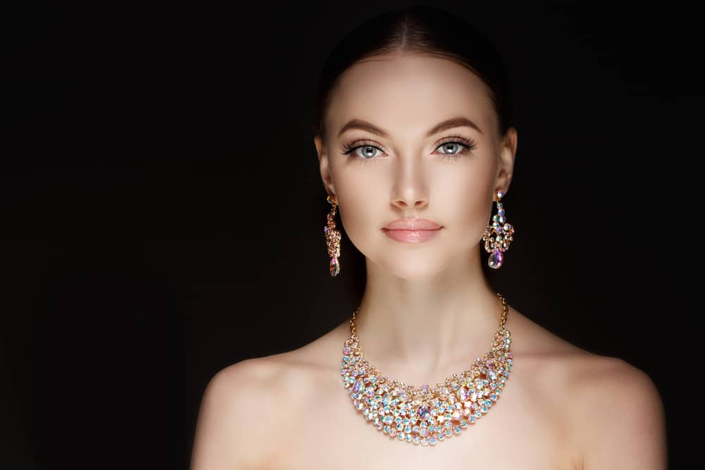 Woman wearing necklace and matching earrings.