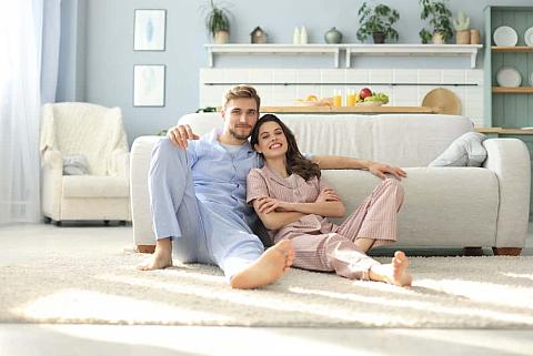 Couple in their pajamas sitting on the floor.