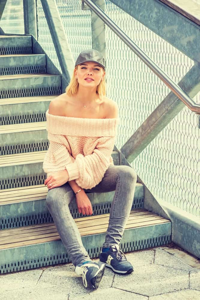 Woman sitting on stairs wearing an off-the-shoulder sweater.