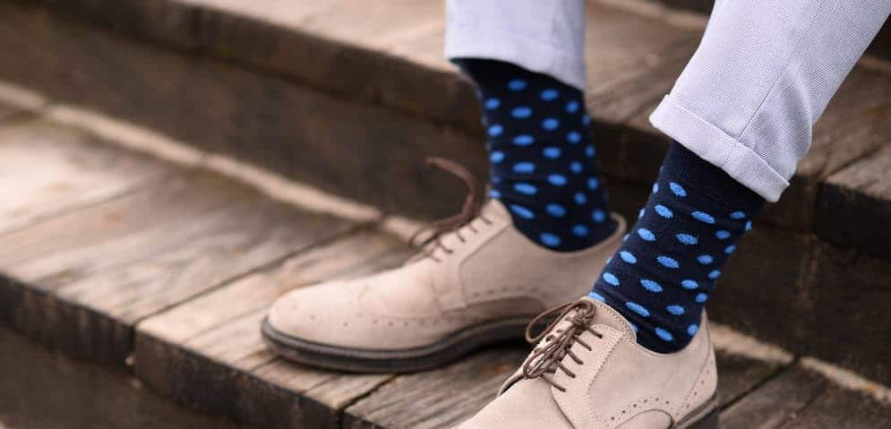 A man wearing colorful patterned socks.