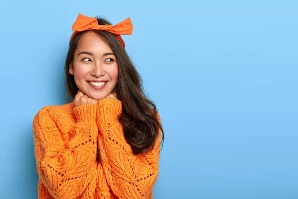 Smiling woman wearing an open knit sweater in bright orange with matching bow headband.