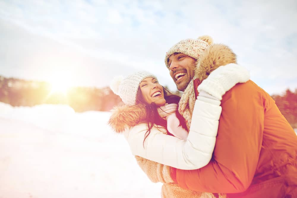 A couple hugging and laughing outdoors during winter.