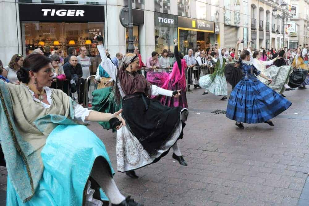 Women in peasant skirts dancing during a parade.