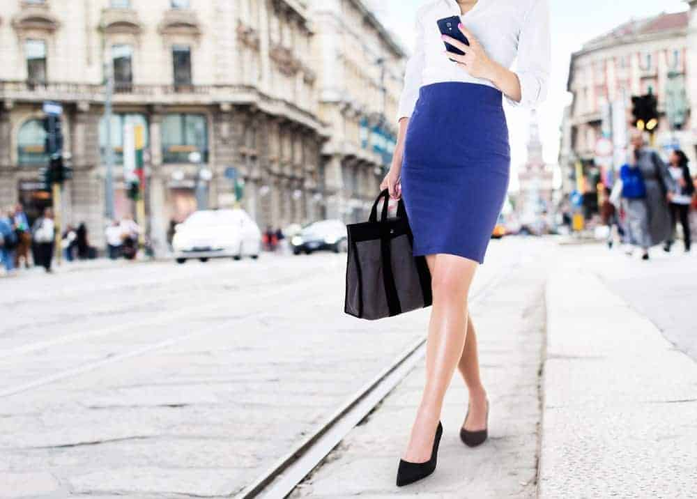 Business woman wearing a white polo and blue pencil skirt.