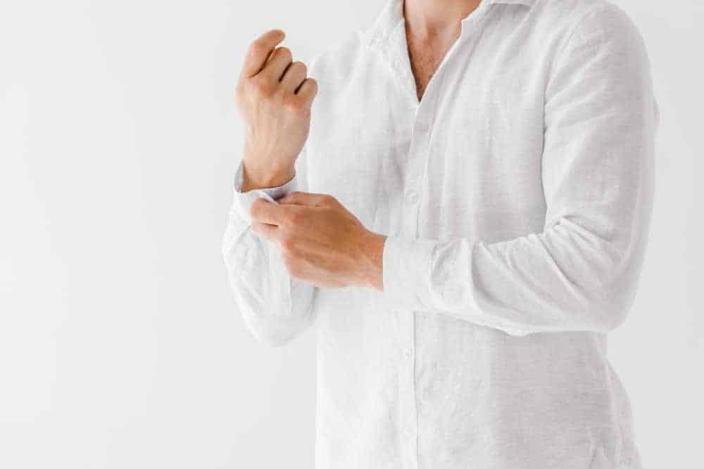 Man wearing a plain white linen shirt on a white background.