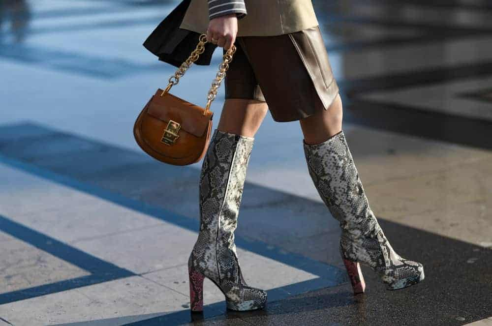 A woman walking down the street wearing a snake print platform boots and brown leather chain bag.