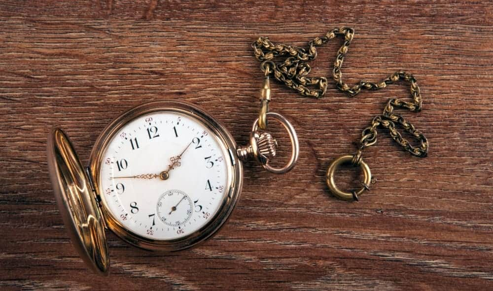 Antique gold pocket watch on a wooden table.