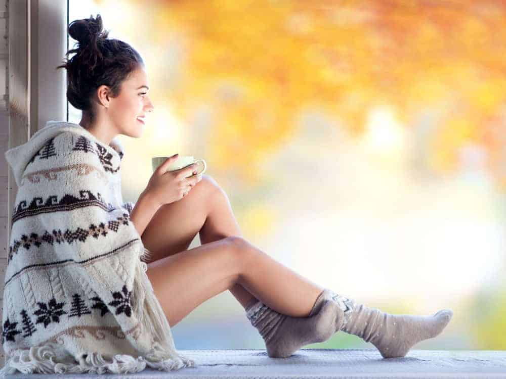 Woman holding a cup of coffee covered in a pancho sweater.