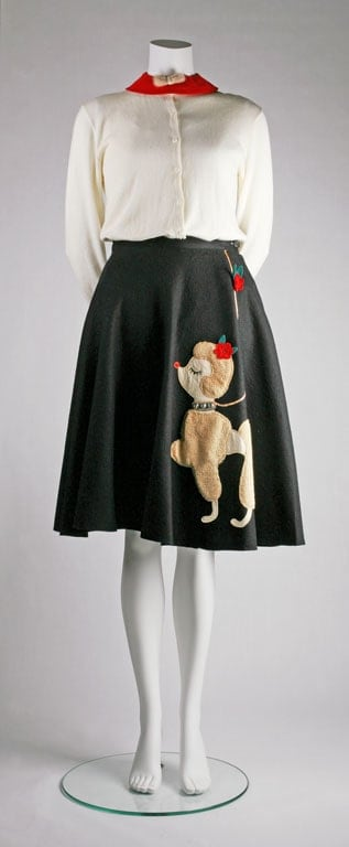 Mannequin dressed in a long sleeve blouse and black poodle skirt.