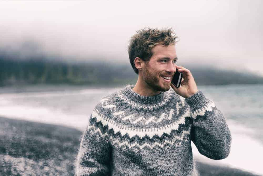 Man in a pullover sweater talking on phone.