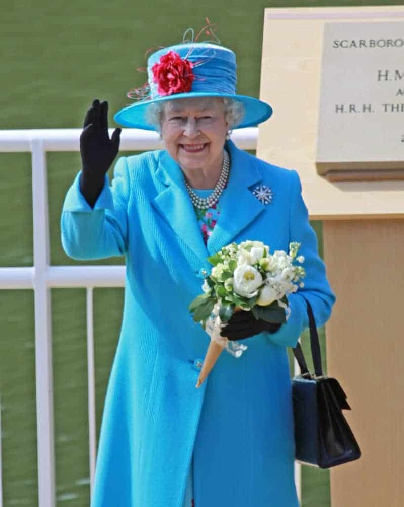 Highness Queen Elizabeth II carrying a black leather handbag.