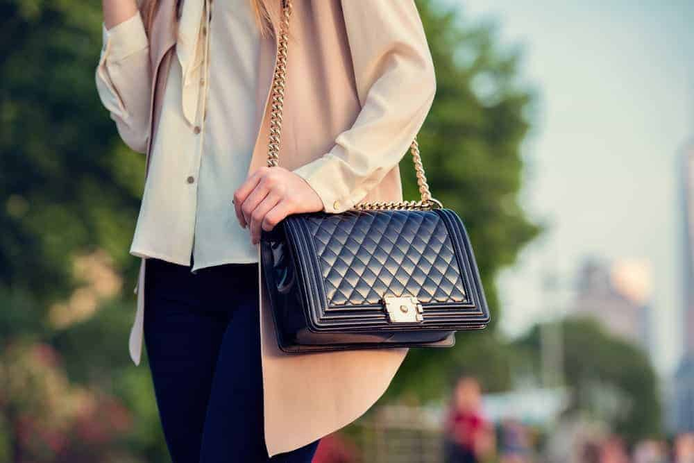 Woman carrying a black quilted bag.