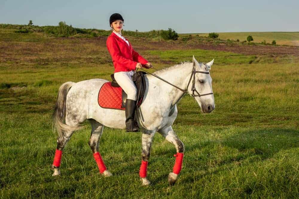 A woman wears a redingote while riding a horse.