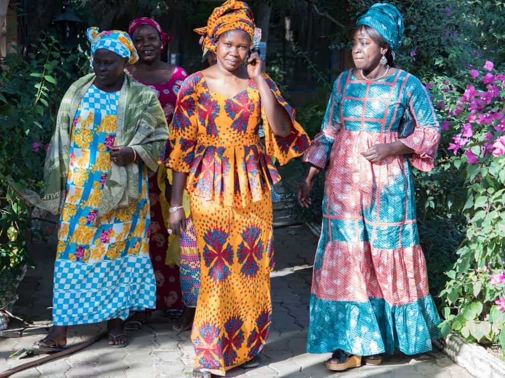 Senegalese women in their traditional costume walking at the park.
