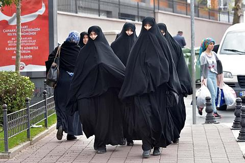 Turkish women in traditional Islamic clothing walking along the city street.