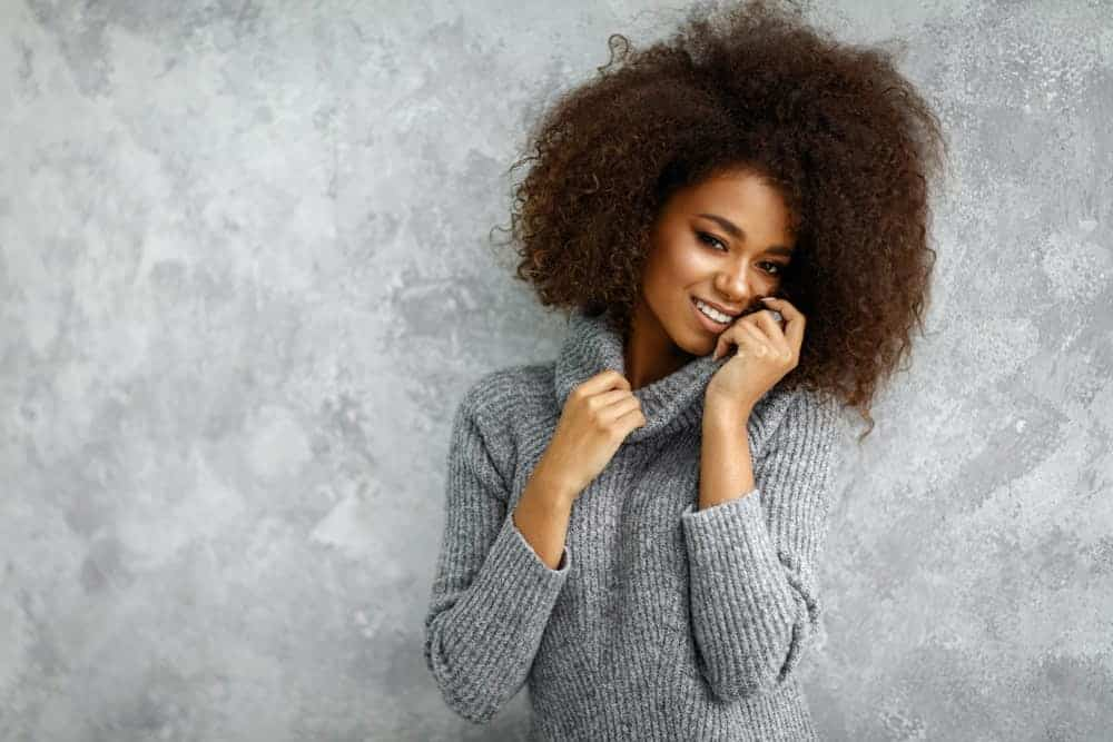 Woman with afro hairstyle wearing a ribbed sweater.