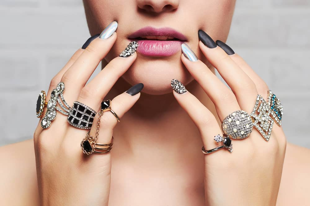 Woman hands filled with jewelry rings.