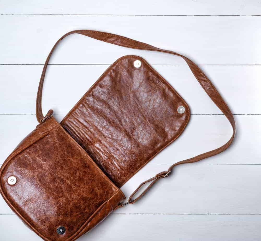 Brown leather saddle bag on a white wood plank background.