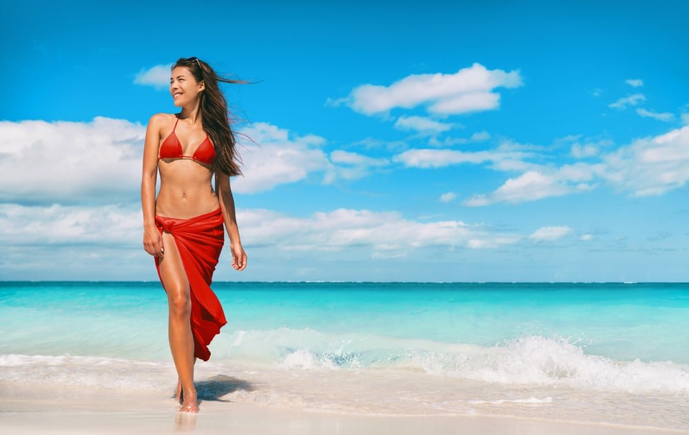 Model in red swimsuit and sarong poses by the beach.