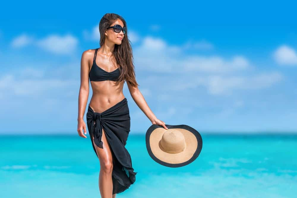 Woman in black swimsuit and sarong standing on the shore.