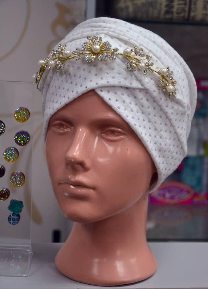 A mannequin head wearing sarpach.