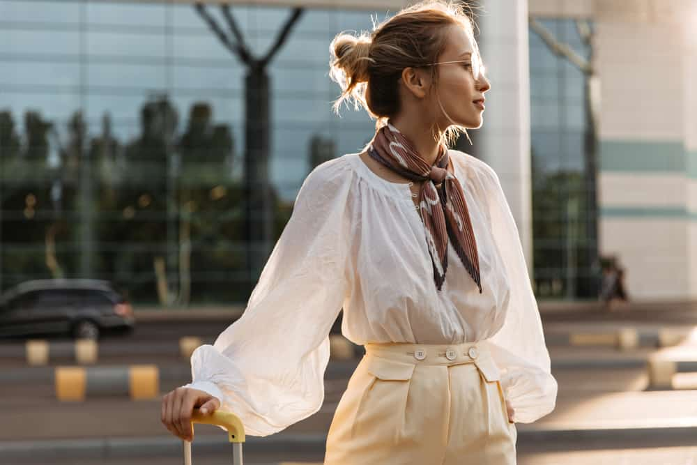 Portrait of blonde girl in white blouse, beige pants, brown silk scarf and eyeglasses holding luggage.