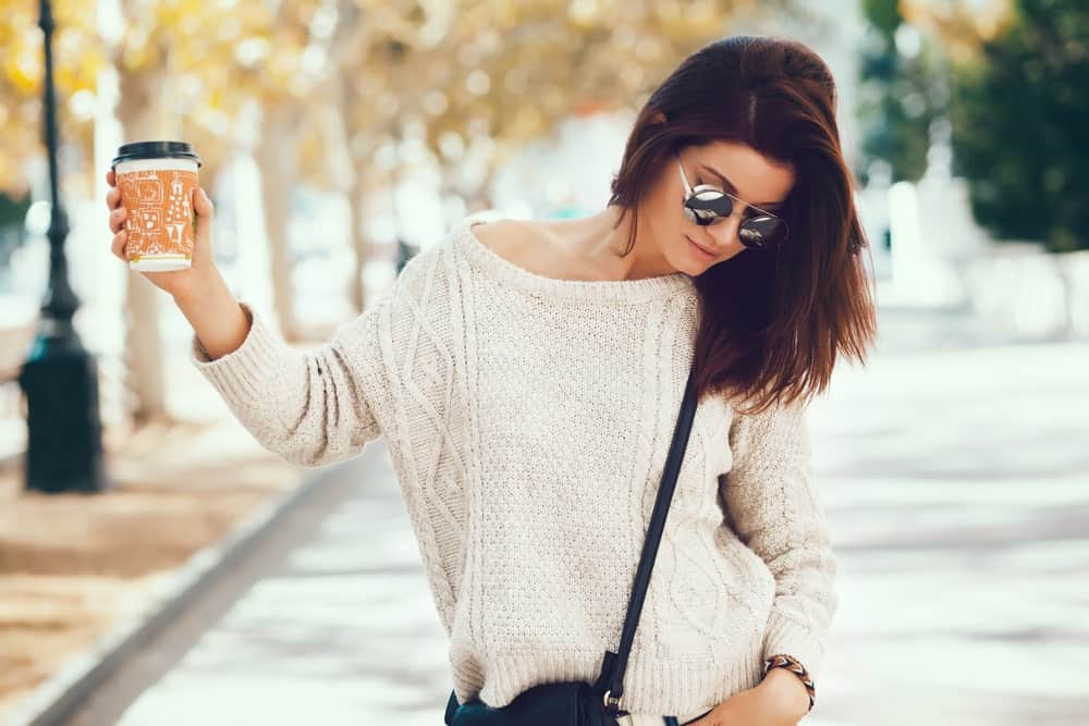 Woman in a scoop neck sweater holding a take away coffee.
