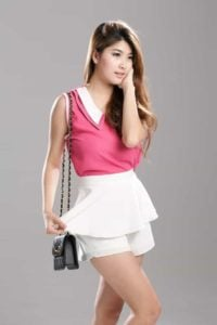 Woman wearing a pink sleeveless top and a white layered skorts.