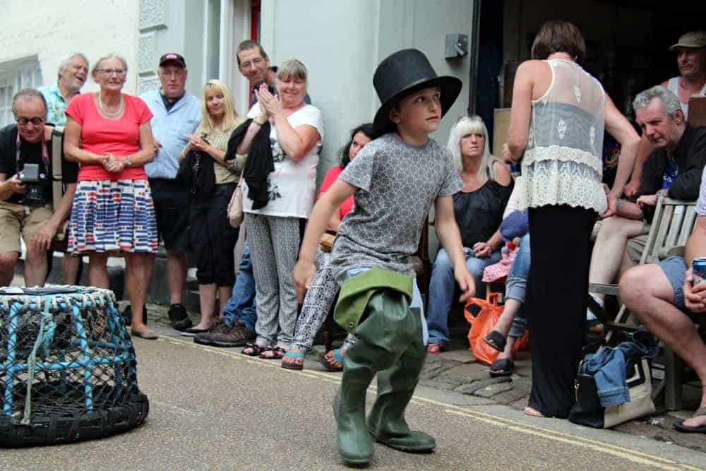 A boy in Courthouse Street wearing a top hat and sea boots.