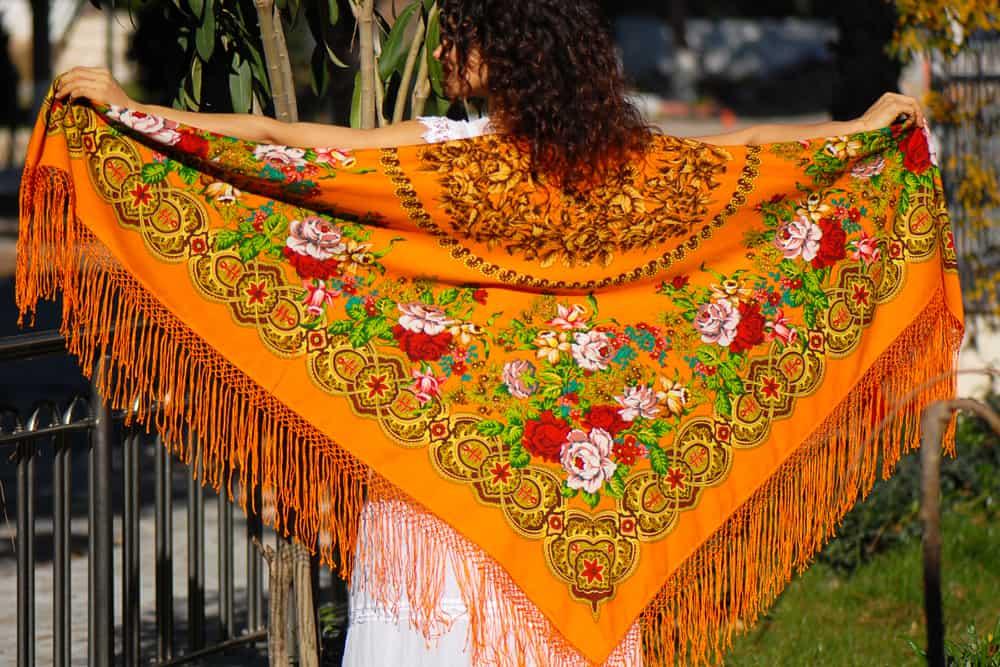 Back profile of a girl holding a tasseled shawl.