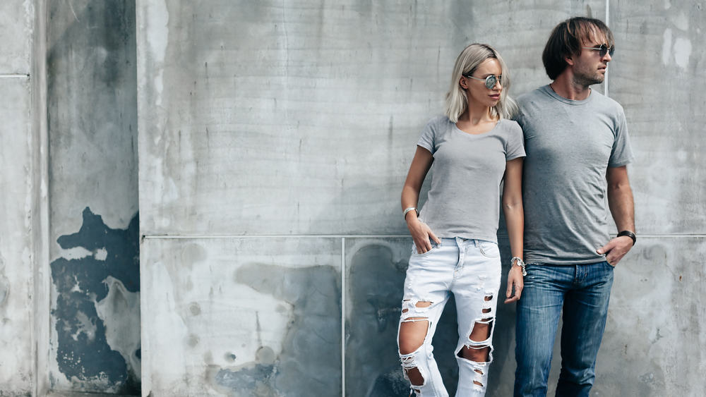 A couple wearing blank gray t-shirt, jeans and sunglasses pose against the concrete wall.