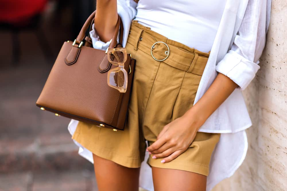Woman wearing linen shorts, white shirt, and brown leather bag with clear glasses.
