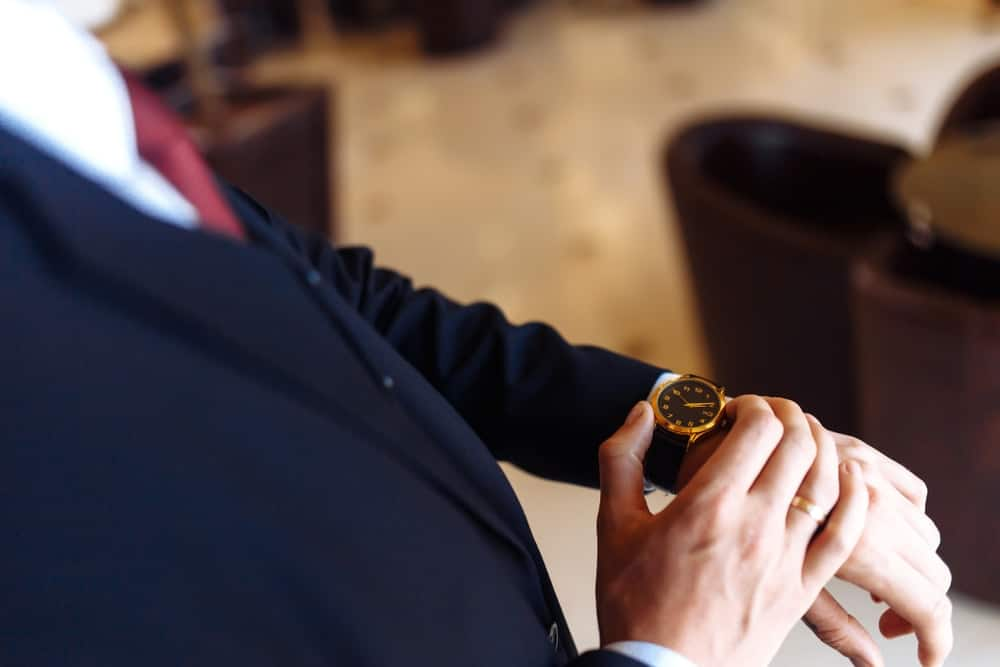 A man in a stylish suit checking the time on his left hand wristwatch.