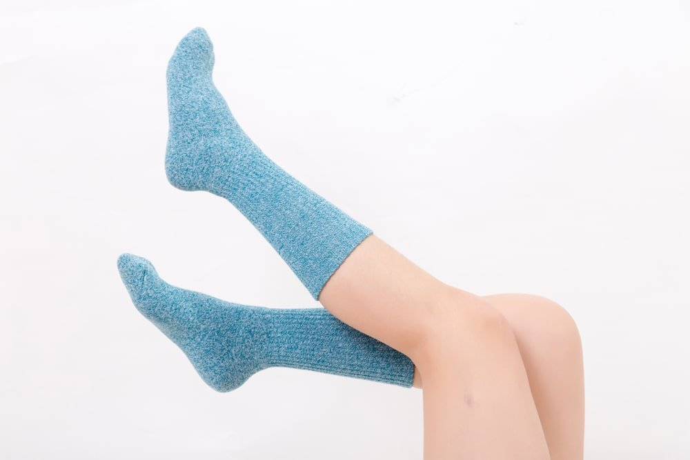 Person wearing blue-green socks on a white background