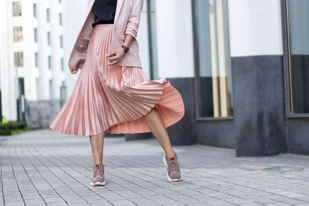 Woman with coral pleated skirt and sneakers.