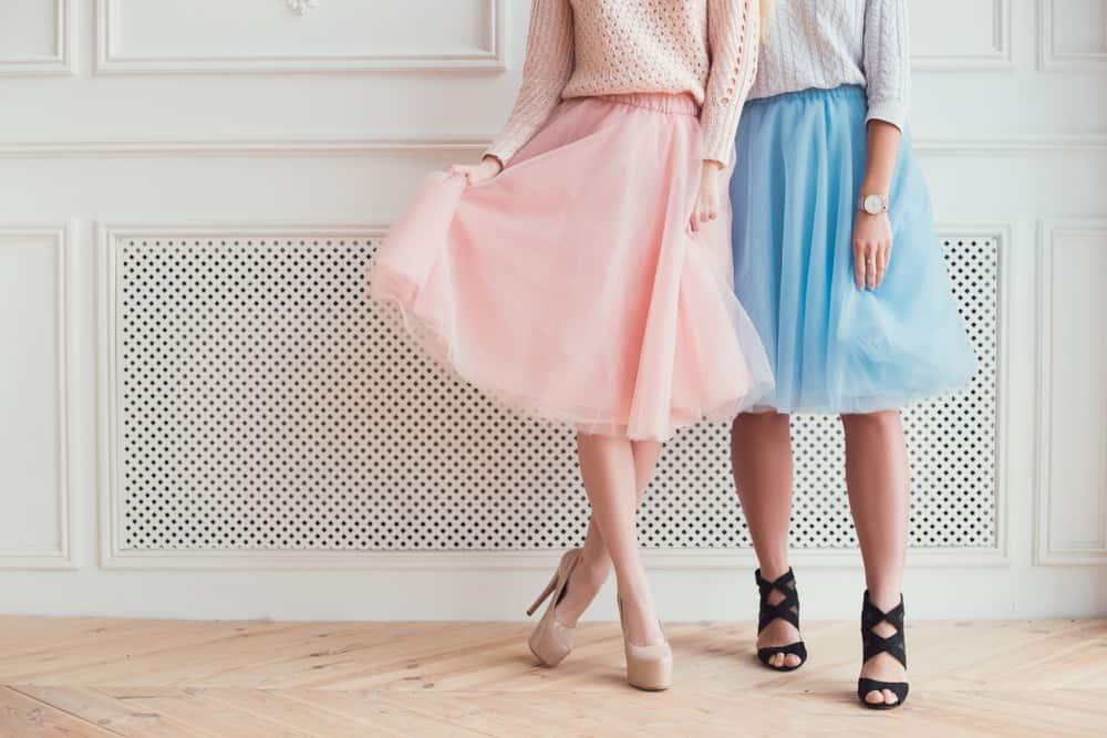 Two girls wearing pastel skirts ad high heels.