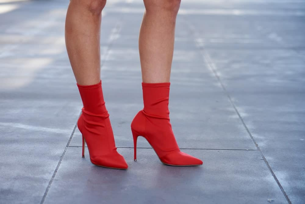 Woman on pavement wearing red sock ankle boots.