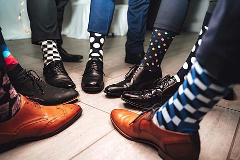Close up of men legs wearing formal shoes and colorful socks.