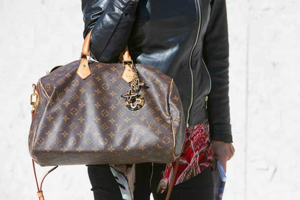 Woman in black leather jacket carrying a Louis Vuitton speedy bag.